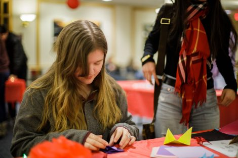 A student makes origami at the Lunar New Year celebration.
