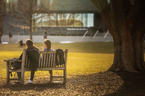 two students talk on a bench