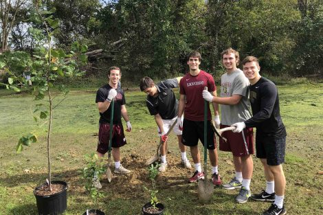 Team members pose with shovels as they dig holes for trees they will plant.