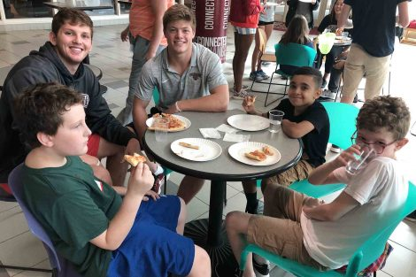 Players eat pizza with three kids from local schools.