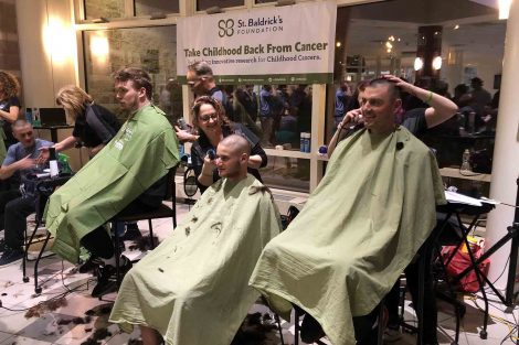 Team members sit in barber chairs as they shave their heads for charity.