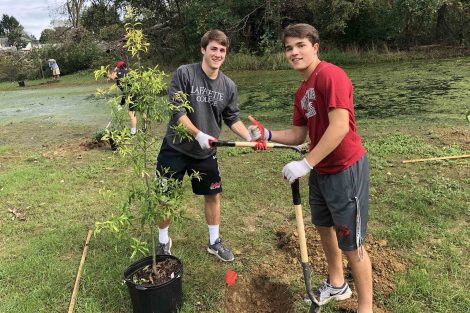 Two Lacrosse players dig holes for trees they plant for Habitat for Humanity.