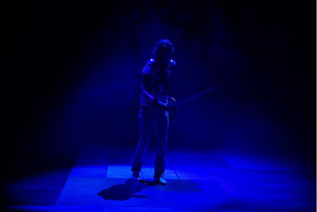 The actress playing Agnes stands in blue light holding a sword