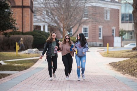 students walk along a brick path