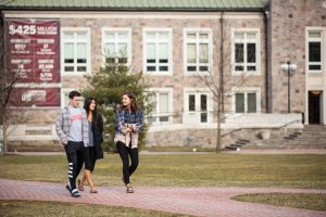 students walk in front of farinon
