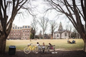 students sit on a bench on the quad