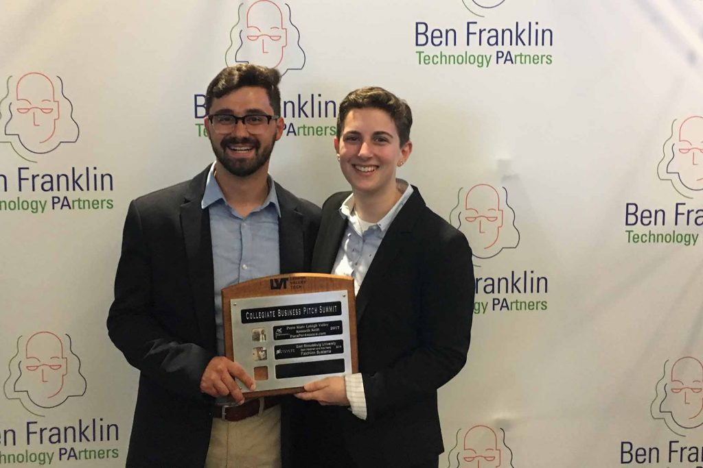 Alexander Homsi '19 and Rebecca Adelman '19 smile as they hold a plaque in front of a Ben Franklin backdrop.