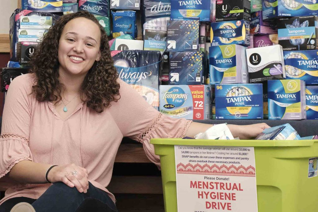 Jazmyn Ball '20 sits in front of stacks and stacks of menstruation products collected in a month-long drive.