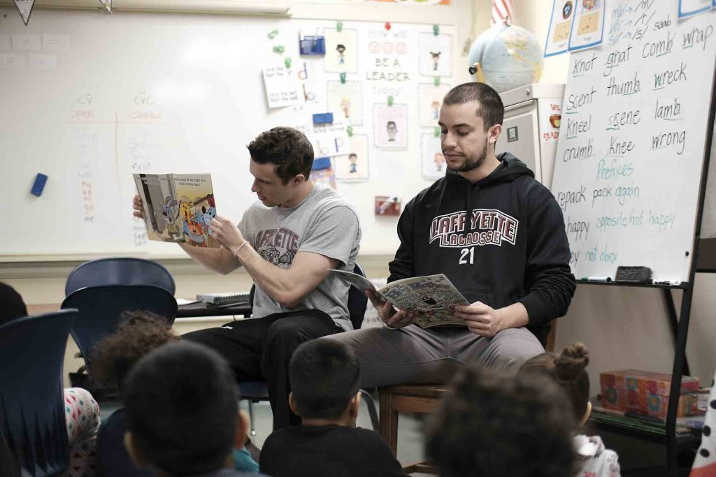 Two lacrosse players take turn reading a book to second graders.