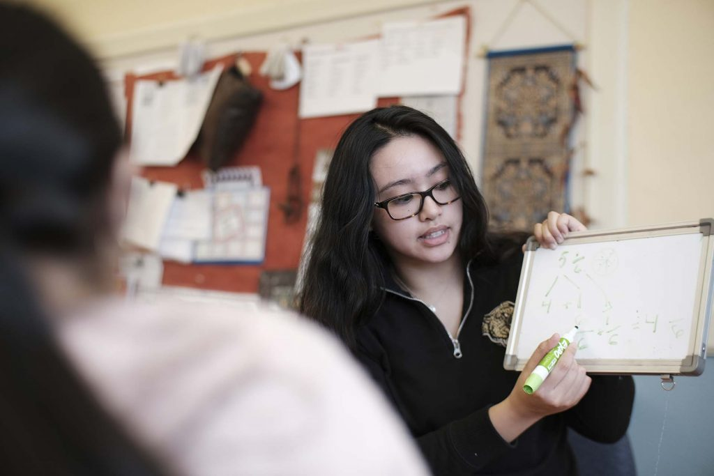 Lafayette student holds up a mini whiteboard and shows how to convert a fraction.