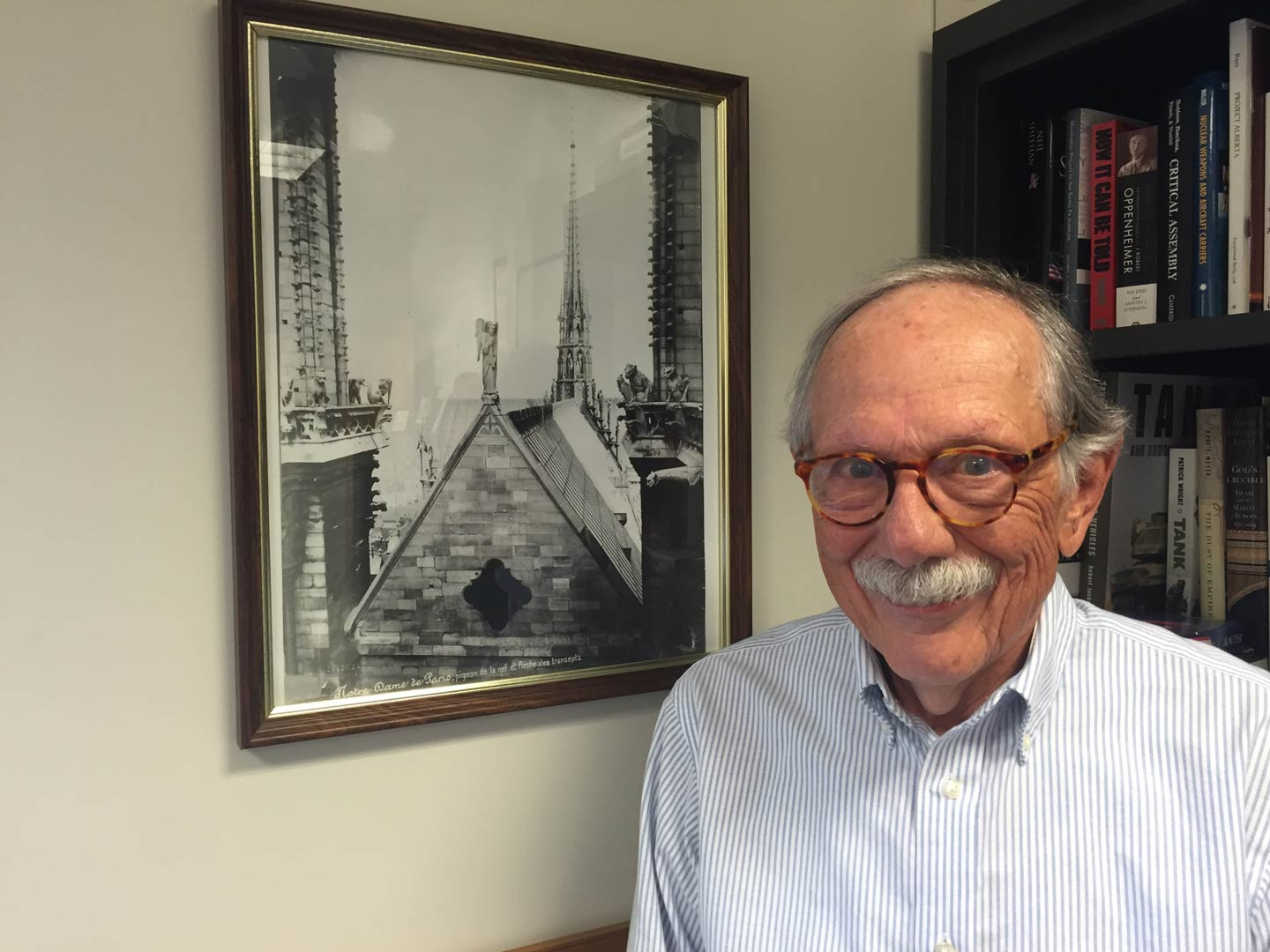 Professor Leonard Van Gulick stands by a photo in his office of Notre-Dame Cathedral in Paris.
