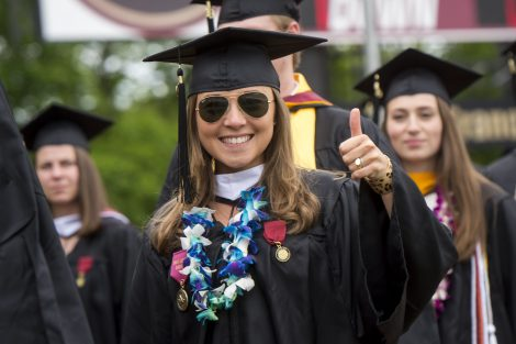 A student gives the thumbs up sign at Commencement.