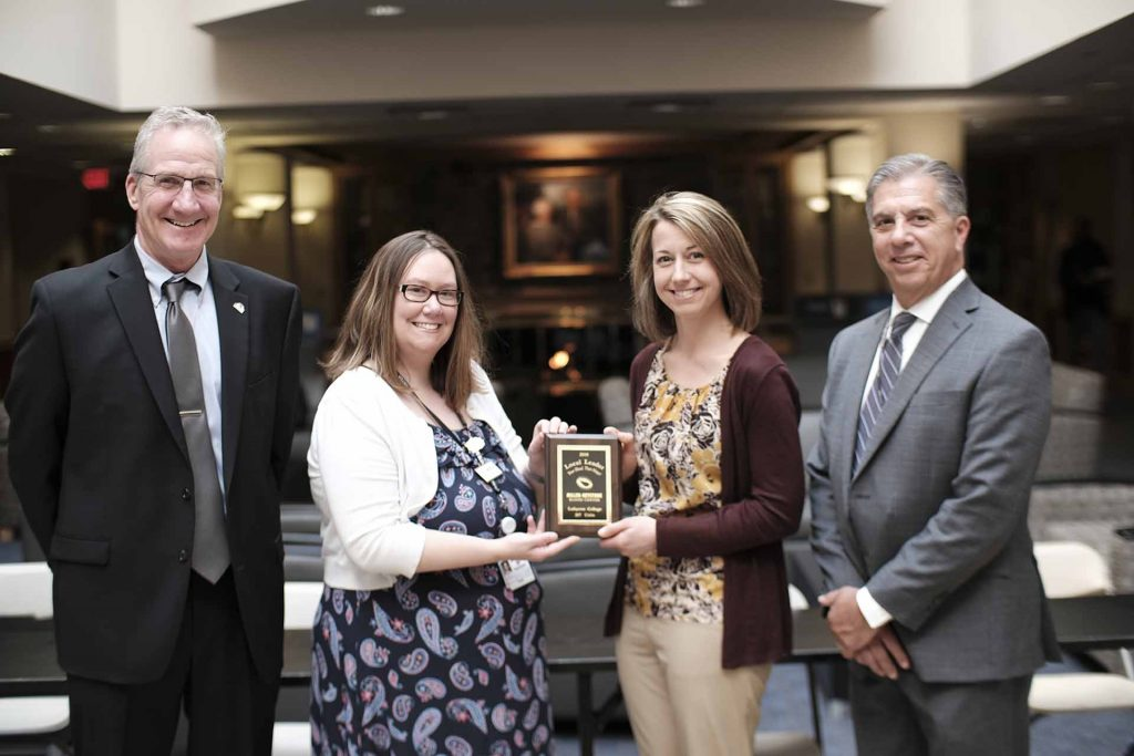 Amber Zuber receives a plaque from Miller-Keystone Blood Center leaders Michael McShane, Krista Hill, and Pete Castagna.