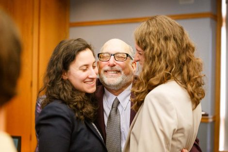 Retiring history professor Bob Weiner hugs two people at his retirement party.