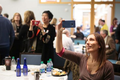 Two guests take photos at retiring history professor Bob Weiner's retirement party.