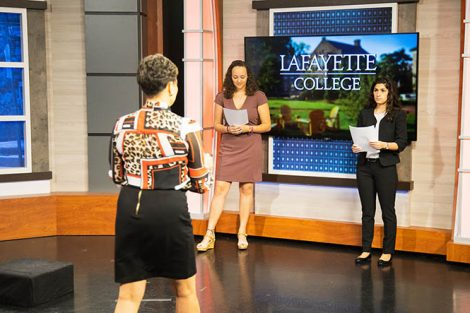 Two students are coached on the set of PBS39 as part of the introduction to Policy Studies program