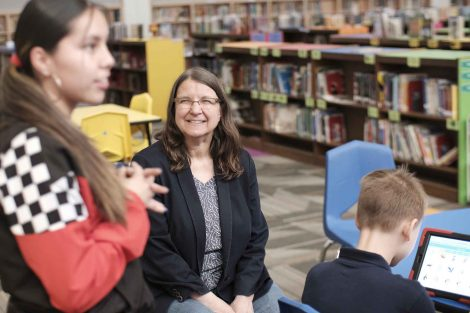 Computer Science Professor Joann Ordille listens as students talk code.
