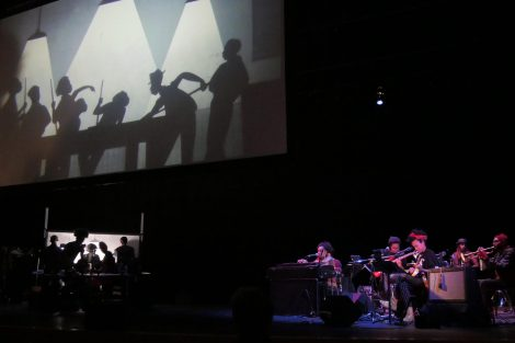 Manual Cinema performers show how the work is made with overhead projectors and musicians