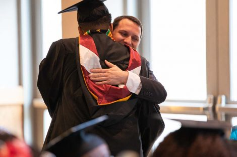 D.C. 8 faculty mentor Josh Smith gets a hug from one of his scholars