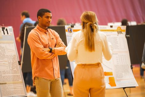 Students explain their research to visitors at the 2019 spring poster session in Kamine Gymnasium in Kirby Sports Center.