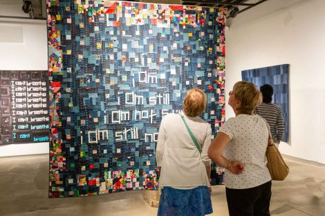 Two guests look at a quilt created by Chawne Kimber, professor of mathematics