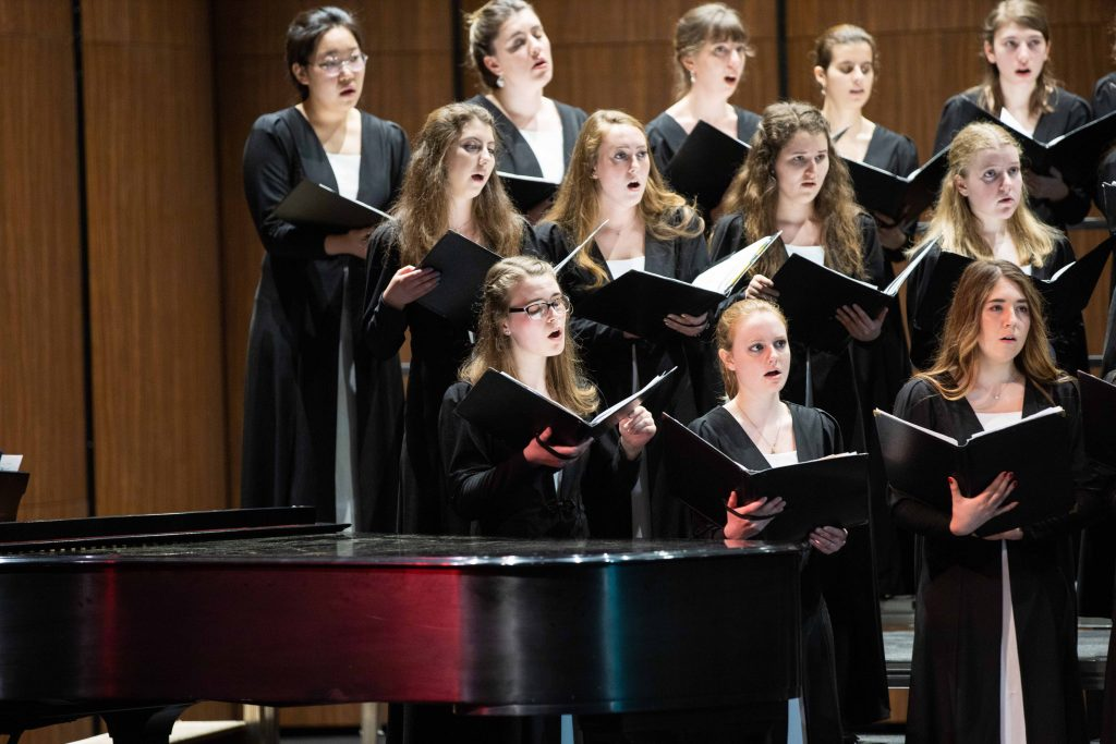 Emily sings with other choir members at a College concert.