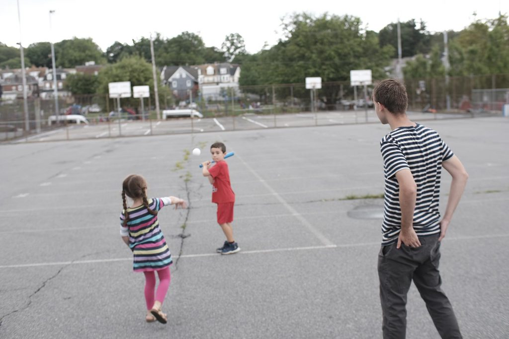 Girl pitches a wiffle ball to her brother as a Lafayette student watches.