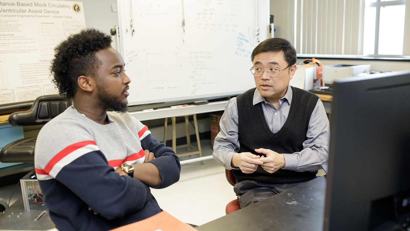 Robson Adem '19 and Yi-Choung Yu talk in a classroom.