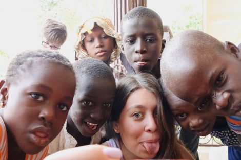 photo of children taking selfie with student in Senegal.