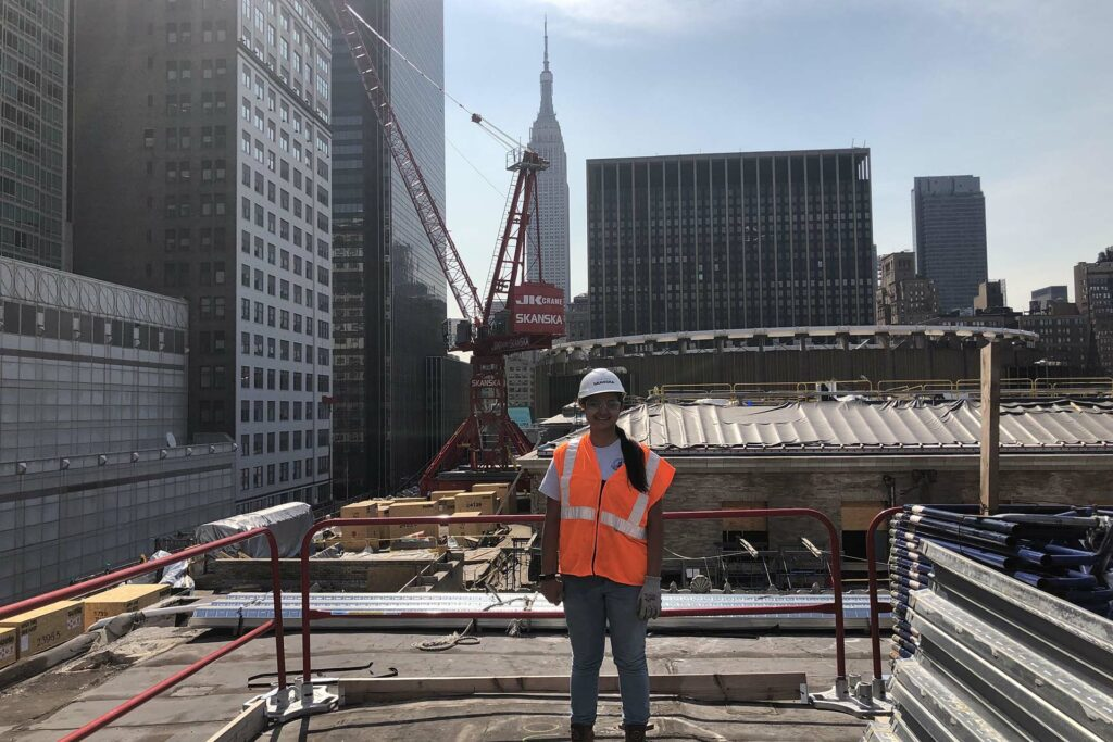 Student in orange vest and white hardhat stands on platform with New York City skyline behind her.