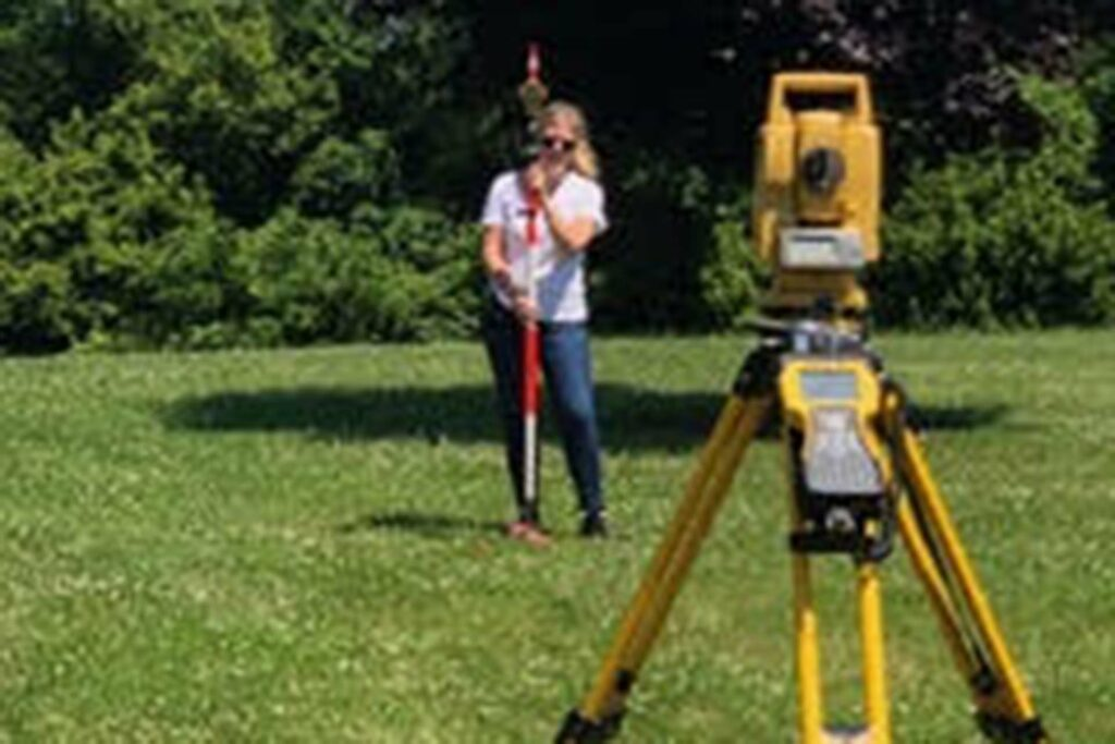 Student stands in grassy yard with survey equipment.