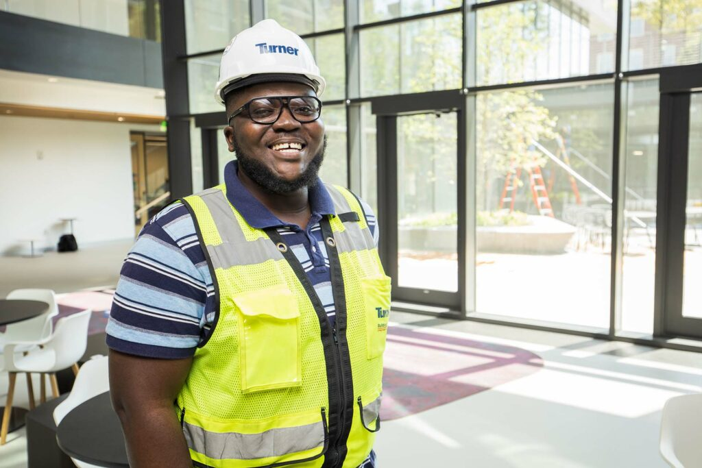 Student in hardhat and vest poses inside the Rockwell Integrated Sciences Center
