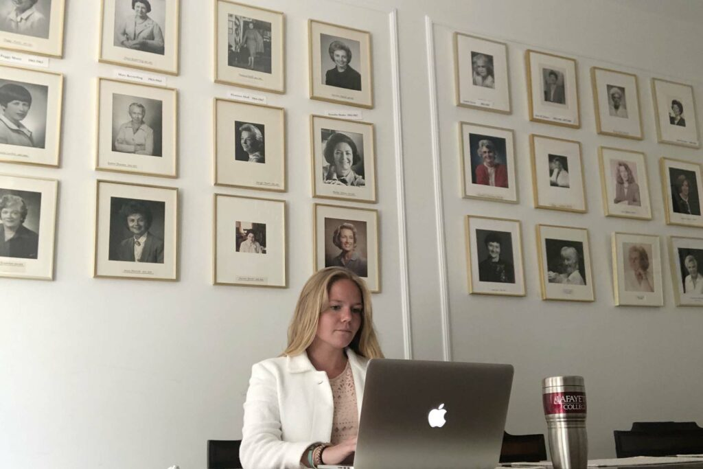Student sits at laptop with a wall of female portraits behind her