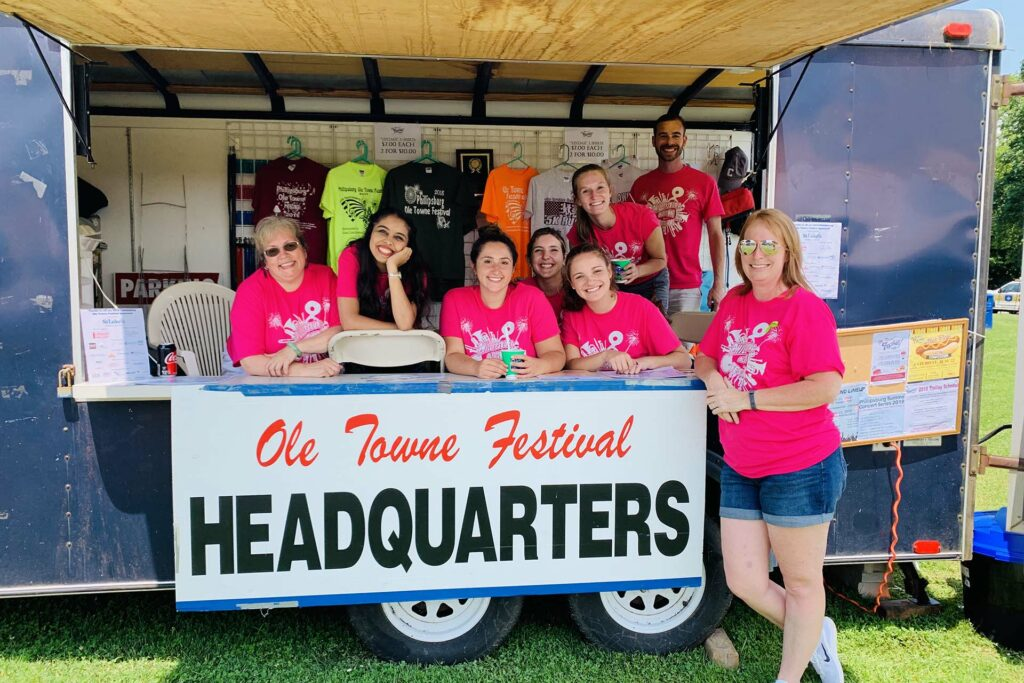 Group in neon pink shirts pose at festival headquarters