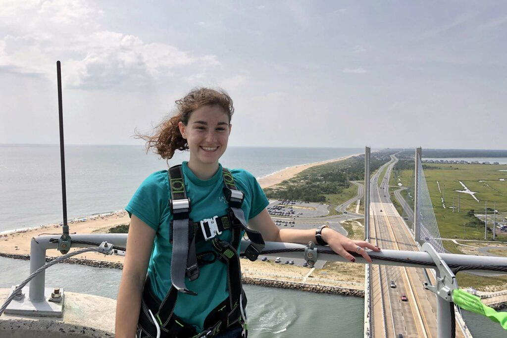 Student poses at the top of a tall bridge in Delaware with the coast behind her
