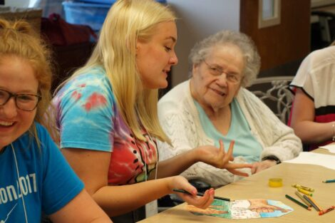 Student speaks with elderly woman as they color together