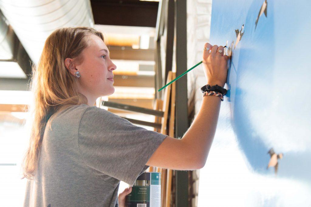Regan Kinney '20 works on the mural