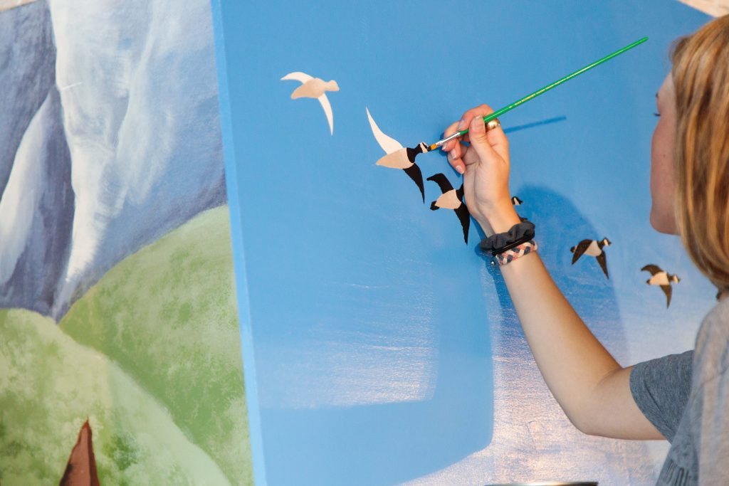 Close up of Regan painting the geese.