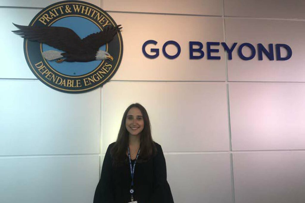 Abbott Price '19 stands in front of an eagle logo and tagline at her new place of employment.