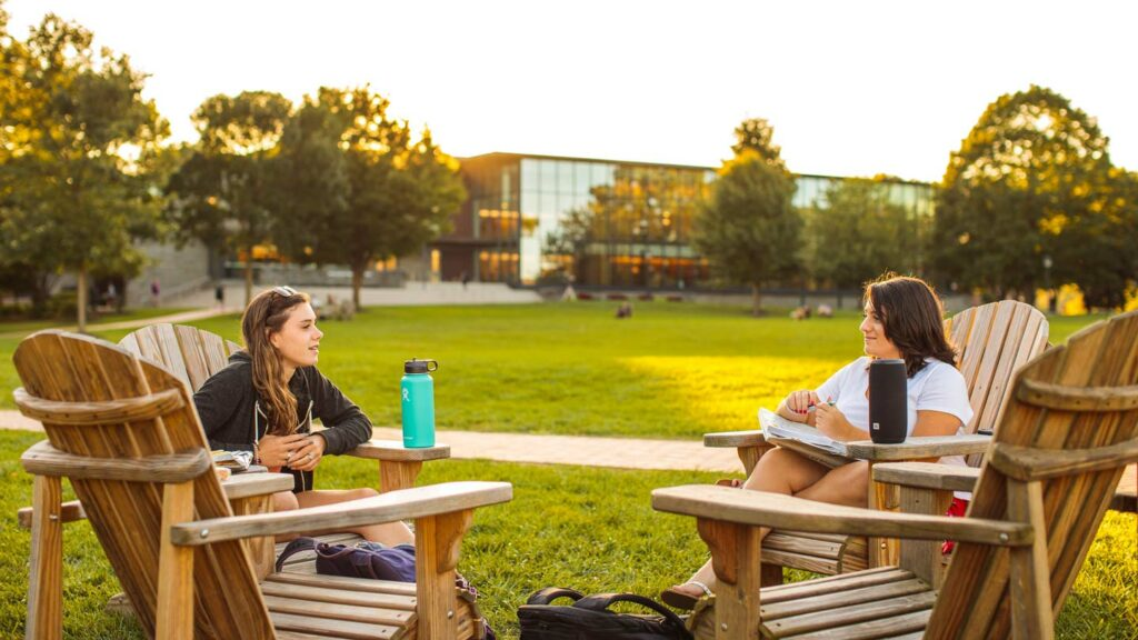 Two students sit in Adirondack chairs on the Quad and talk.