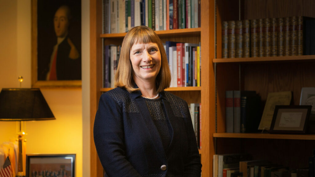 Lafayette College President Alison Byerly stands in front of a bookshelf in her office.