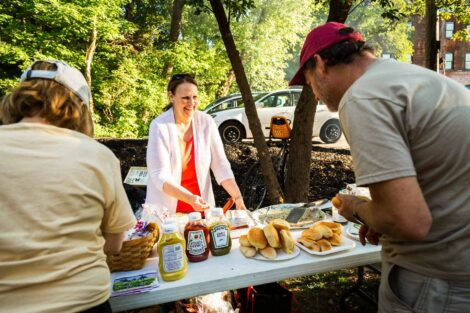 Volunteers serve hot dogs and hamburgers on the trail with a side of grasshoppers