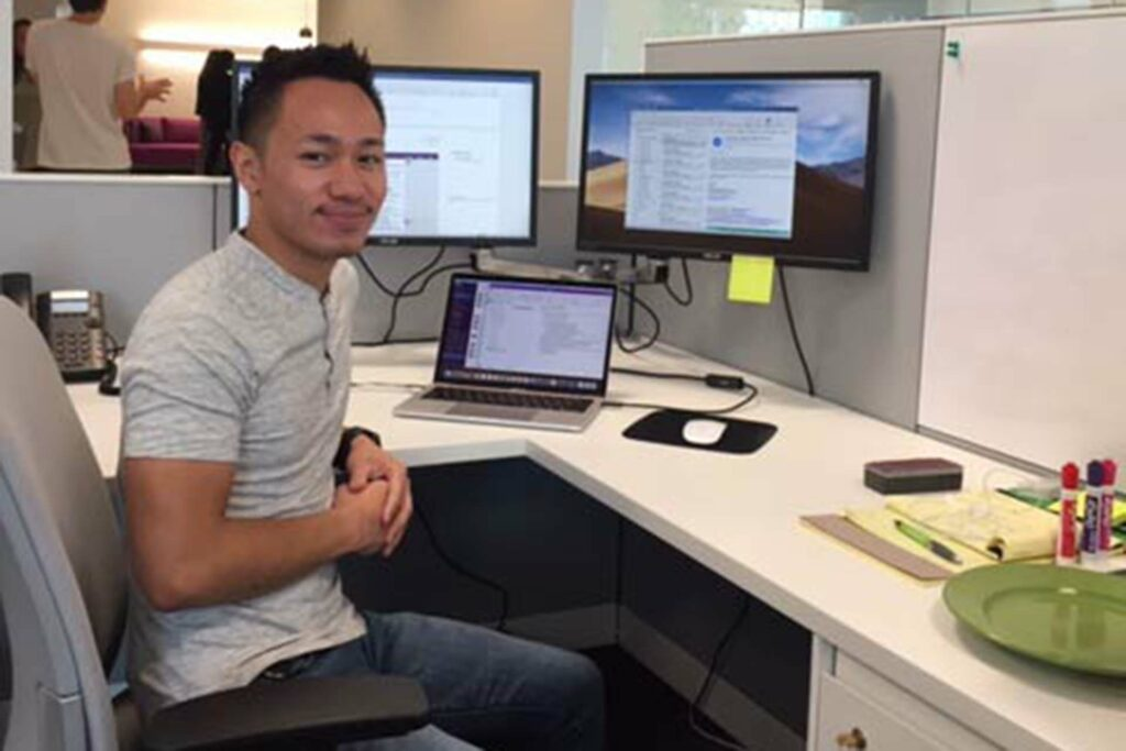 Chris Panaguiton '19 sits at his desk at his alumni employer