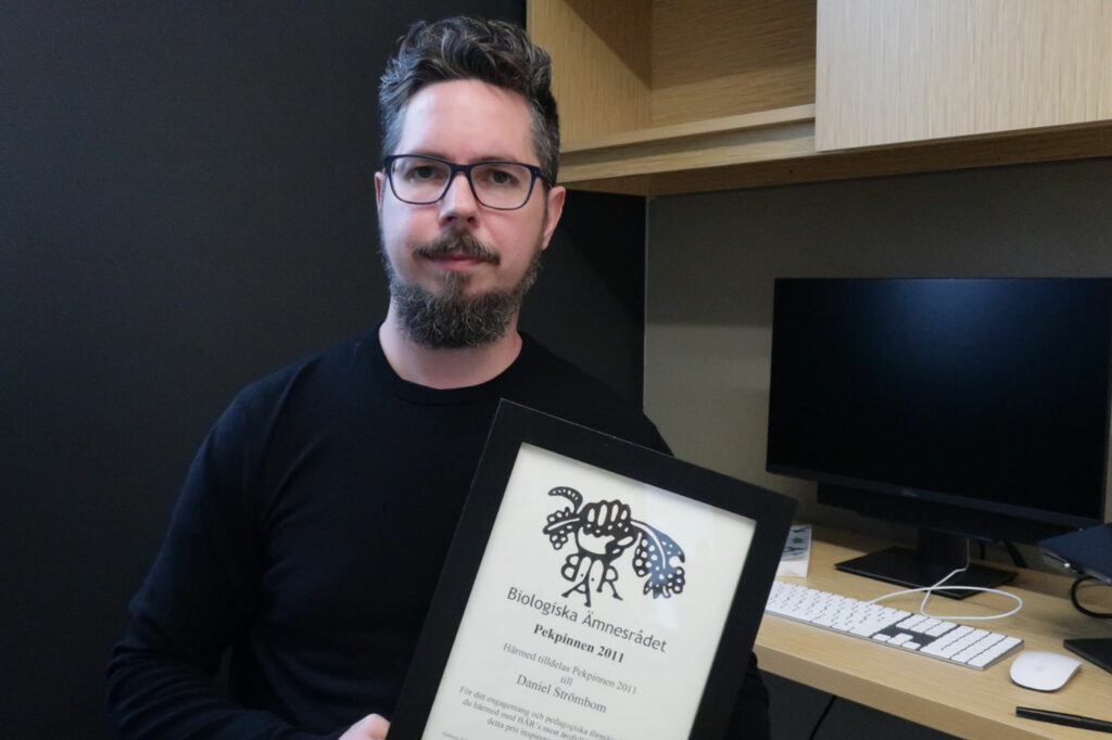 Daniel Strömbom holds a framed certificate for a teaching award given to him by biology students.