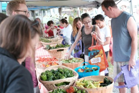 Residents buy produce at the Farm Stand run by the Vegetables in the Community program.