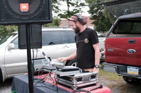 A DJ plays music at the Farm Stand run by the Vegetables in the Community program.
