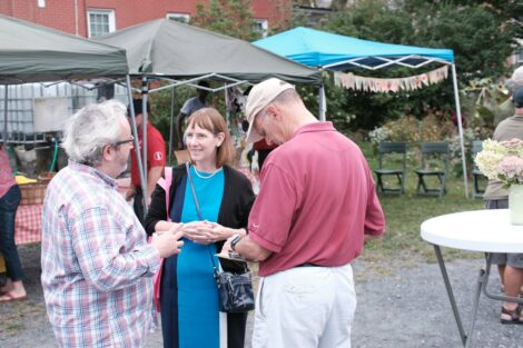 Professors Ben Cohen and Larry Malinconico talk with Lafayette College President Alison Byerly at the Farm Stand run by the Vegetables in the Community program.