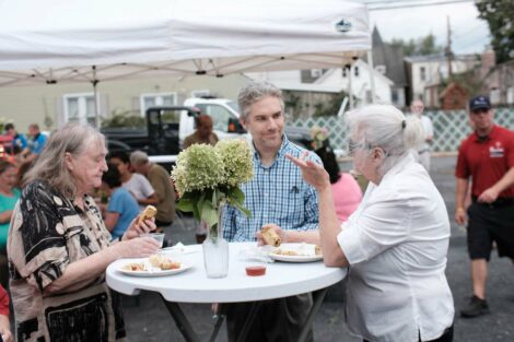 Residents eat dinner and talk at the Farm Stand run by the Vegetables in the Community program.