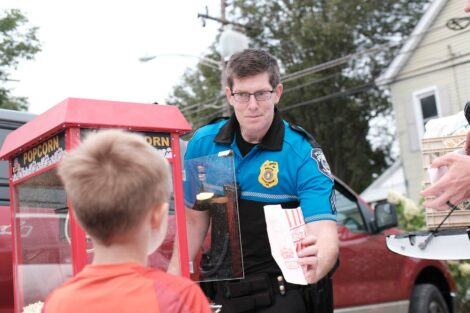A police officer gives a bag of popcorn to a child at the Farm Stand run by the Vegetables in the Community program.