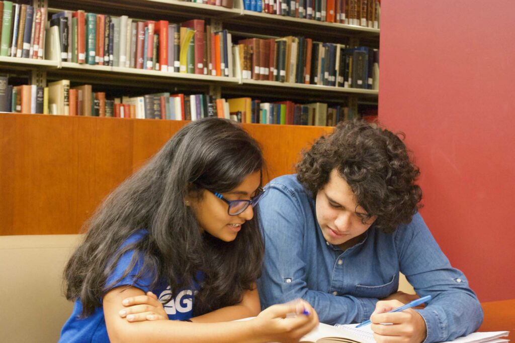 GoPeer tutor helps a student as they lean over a book and papers.